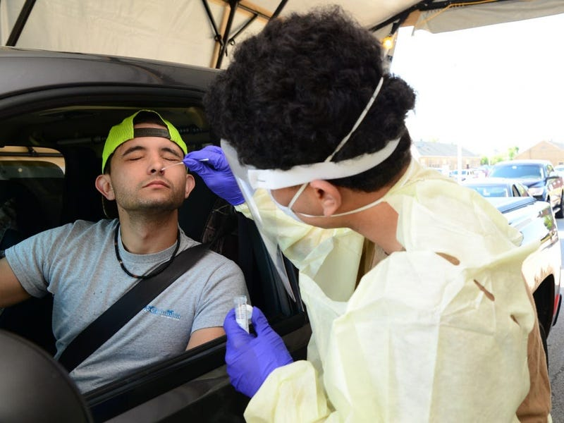 Captain James A. Lovell Federal Health Care Center Hospitalman Recruit Yavir Berrios-Santiago collects a nasal swab from a Naval Station Great Lakes Recruit Training Command employee during drive-through COVID-19 screening at Lovell FHCC in North Chicago.