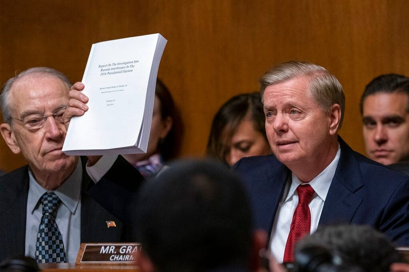 Senate Judiciary Committee Chairman Lindsey Graham, R-S.C., right, joined at left by Sen. Chuck Grassley, R-Iowa, raises a copy of Mueller report, during his opening statement before swearing-in Attorney General William Barr to testify, on Capitol Hill in