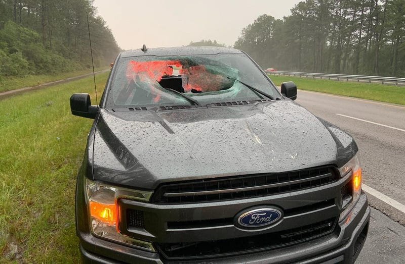 Damage caused to a Ford truck after a lightening bolt send chucks of the pavement through the front and back windshield