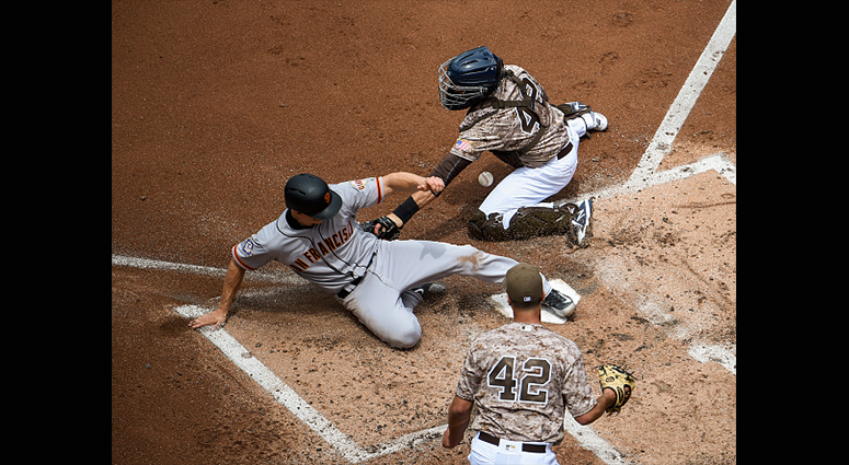 APRIL 15: Nick Hundley #5 of the San Francisco Giants, (L) scores ahead of the tag of Austin Hedges #18 of the San Diego Padres, (R) as Joey Lucchesi looks on during the second inning of a baseball game at PETCO Park on April 15, 2018 in San Diego, Califo