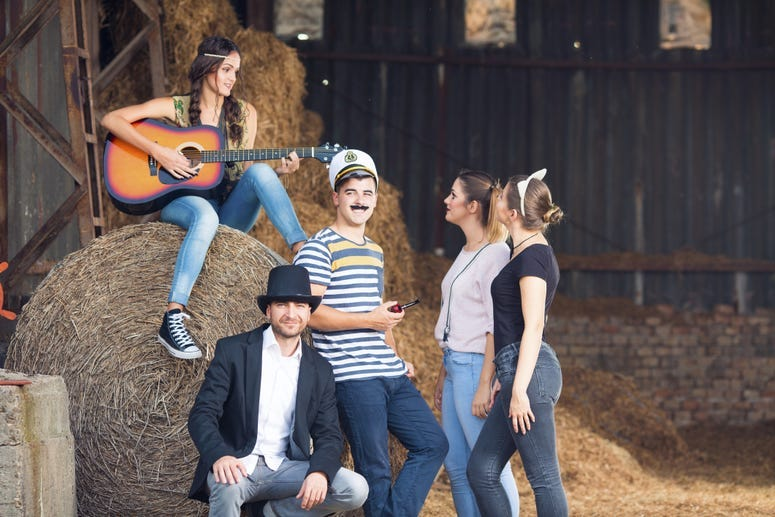 Group of friends wear costumes around a bale of hay