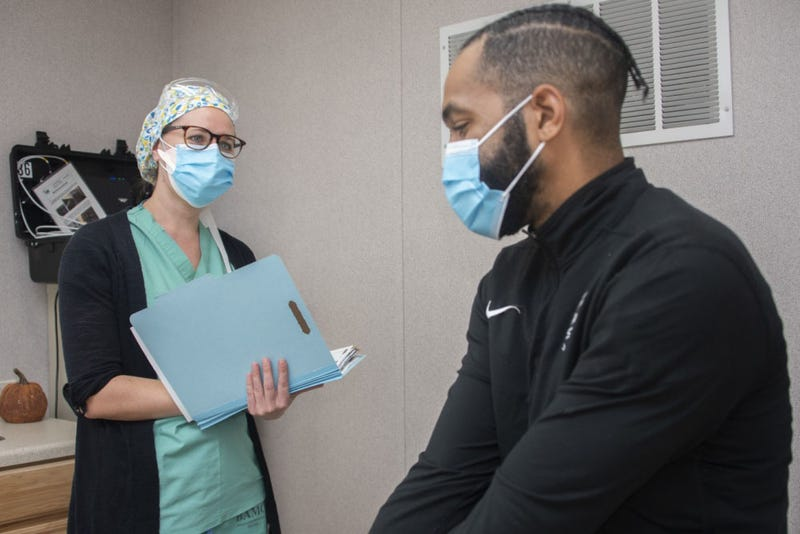 Alfiya Mityukova, a registered nurse, and Roderick Johnson, a research assistant, demonstrate patient screening for the Operation Warp Speed COVID-19 vaccine trial at Brooke Army Medical Center, Fort Sam Houston, Texas, Nov. 16, 2020.