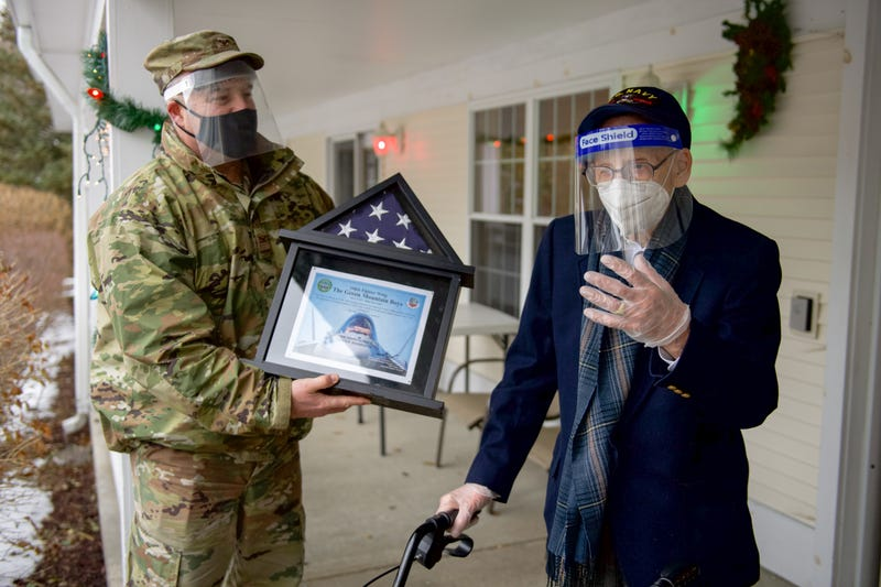 Col. Adam Rice, vice wing commander of the 158th Fighter Wing, Vermont Air National Guard, presents a flag flown in the F-35A Lightning II to WWII veteran Lenny Roberge, Vermont's oldest living veteran.