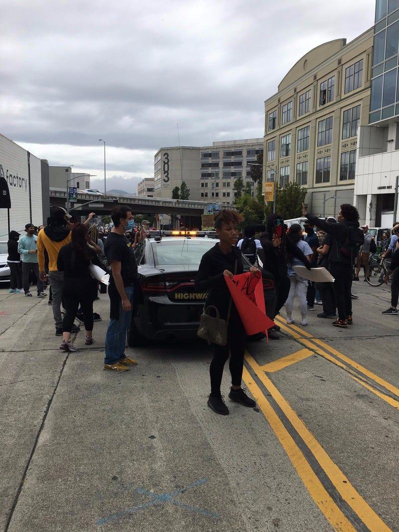 Demonstrators protect a police vehicle at a San Francisco rally.