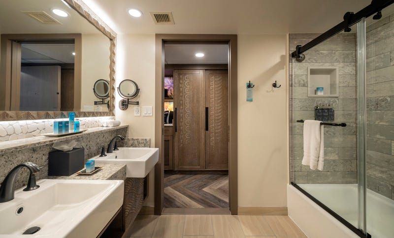 A bathroom in the reimagined guest rooms inside Disney's Polynesian Village Resort at Walt Disney World Resort in Lake Buena Vista, Fla., takes inspiration from the sandy ocean floor for the bathroom tiles and vanity's carved details.