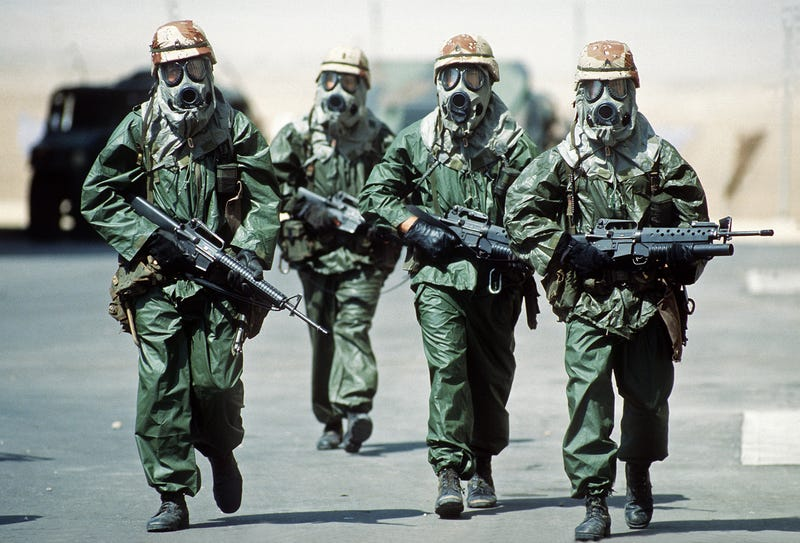 Four soldiers from the 82nd Airborne Division walk around their camp wearing rain suits, gloves and M-17A1 protective masks as they try to acclimate their bodies to the heat of the Saudi summer during Operation Desert Shield.