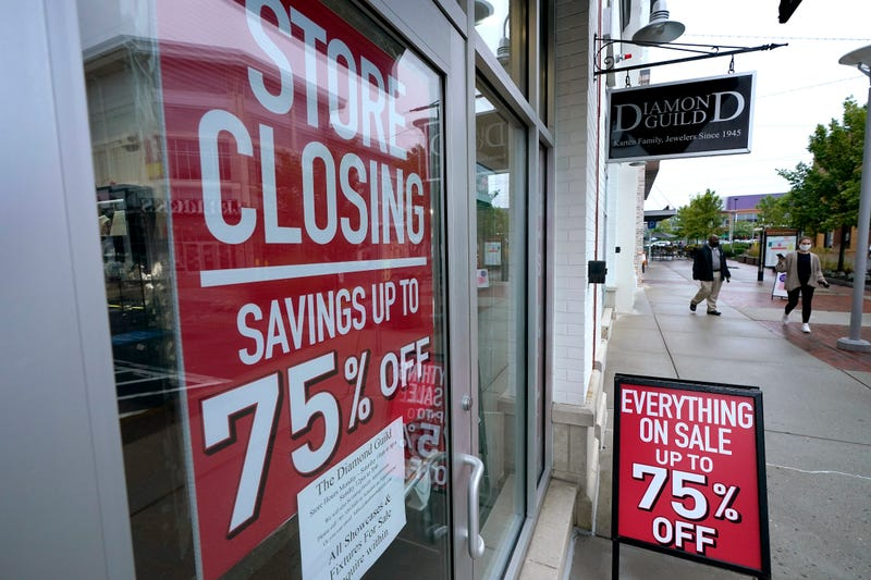 In this Wednesday, Sept. 2, 2020, file photo, passers-by walk past a business storefront with store closing and sale signs in Dedham, Mass.