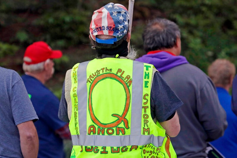 In this May 14, 2020, file photo, a person wears a vest supporting QAnon at a protest rally in Olympia, Wash., against Gov. Jay Inslee and Washington state stay-at-home orders made in efforts to prevent the spread of the coronavirus. President Joe Biden's inauguration has sown a mixture of anger, confusion and disappointment among believers in the baseless QAnon conspiracy theory. (AP Photo/Ted S. Warren, File)