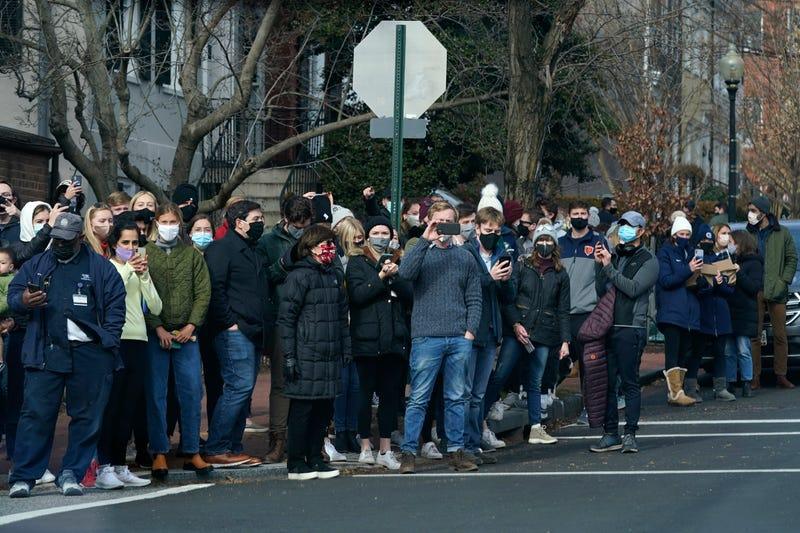 People gather to watch as President Joe Biden's motorcade departs Holy Trinity Catholic Church, Sunday, Jan. 24, 2021, in the Georgetown neighborhood of Washington.