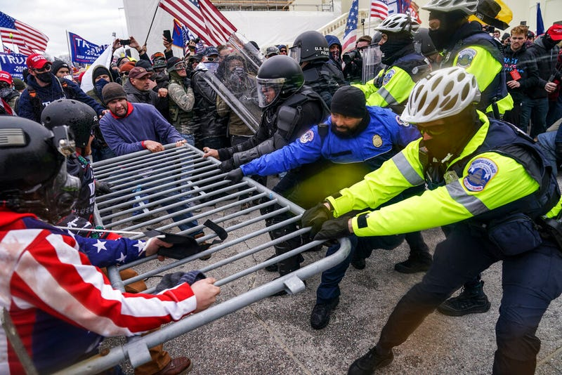 In this Jan. 6, 2021, file photo violent insurrectionists loyal to President Donald Trump supporters try to break through a police barrier at the Capitol in Washington. A month ago, the U.S. Capitol was besieged by Trump supporters angry about the former president's loss. While lawmakers inside voted to affirm President Joe Biden's win, they marched to the building and broke inside. (AP Photo/John Minchillo, File)