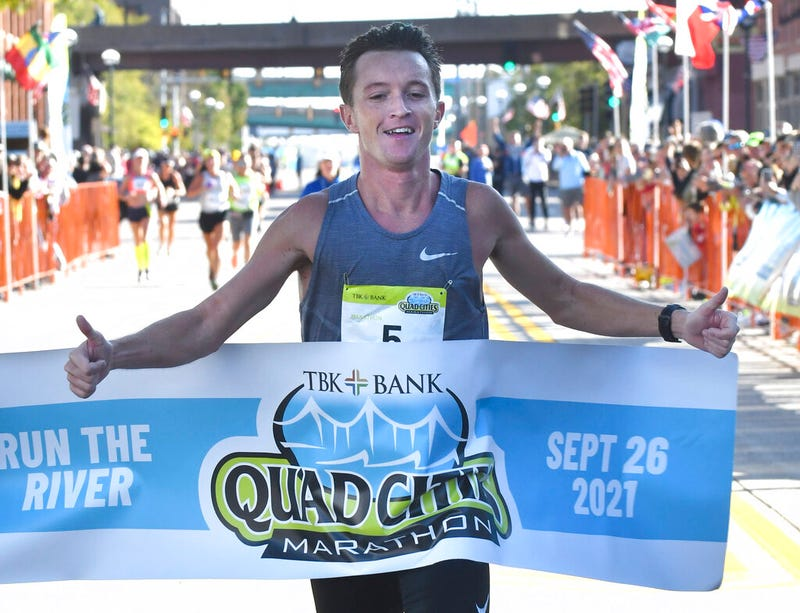 Tyler Pence of Springfield, Ill., finishes first in the TBK Bank Quad Cities Marathon on Sunday, Sept. 26, 2021, in Moline, Ill. An Illinois man unexpectedly won the Quad Cities Marathon this weekend when the two Kenyan runners who had far outpaced him were disqualified after being diverted off the course by a race volunteer bicyclist. Tyler Pence crossed the finish line in 2 hours, 15 minutes, 6 seconds to become the first U.S. runner since 2001 to win the race.