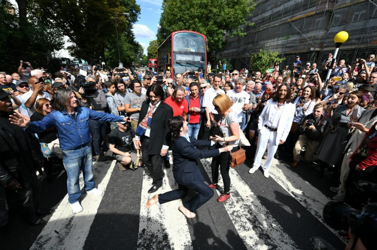 A Paul McCartney impersonator proposes to his girlfriend as a group of Beatles look-alikes recreate the iconic 'Abbey Road' photograph