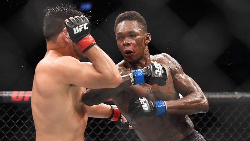 Israel Adesanya strikes Kelvin Gastelum during their interim middleweight title bout at UFC 236.