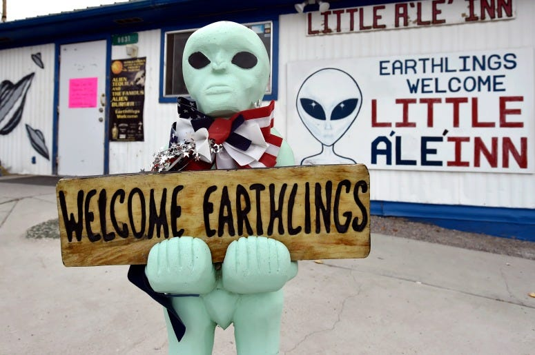 An alien-like statue displays a sign welcoming guests