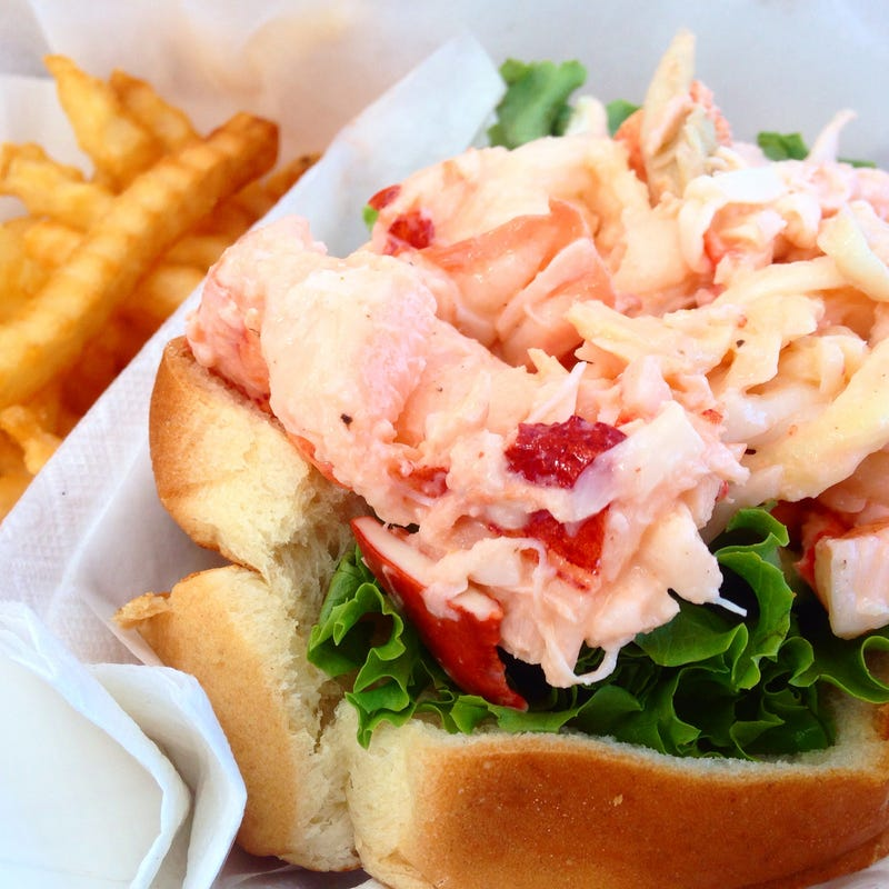 A lobster roll loaded with chunks of lobster meat on a bed of lettuce, with fries on the side nearby.