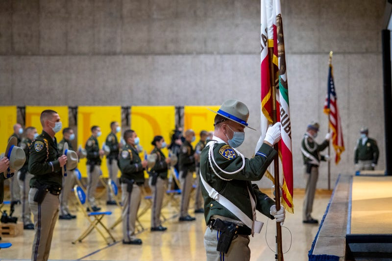CHP graduates stand for the flag.