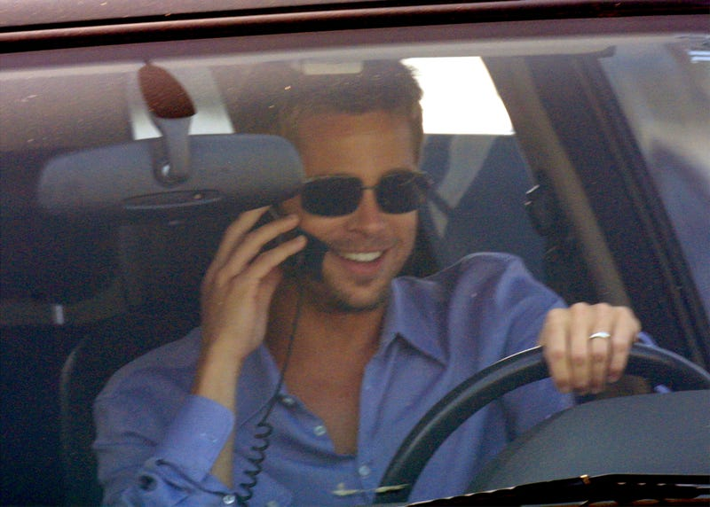 Brad Pitt driving a car and talking on a car phone