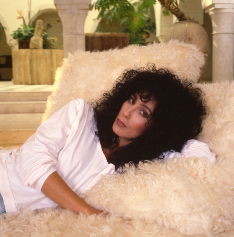 Portrait of American singer and actress Cher as she lies on a fuzzy couch, Los Angeles, California, 1987.