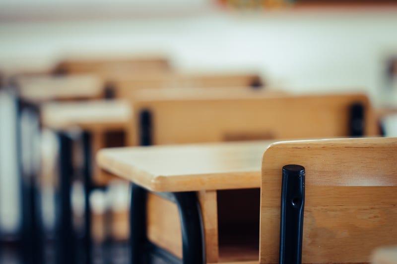 A row of desks in an empty classroom