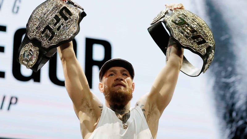 Conor McGregor holds up two UFC belts at a press conference before facing Khabib Nurmagomedov at UFC 229.