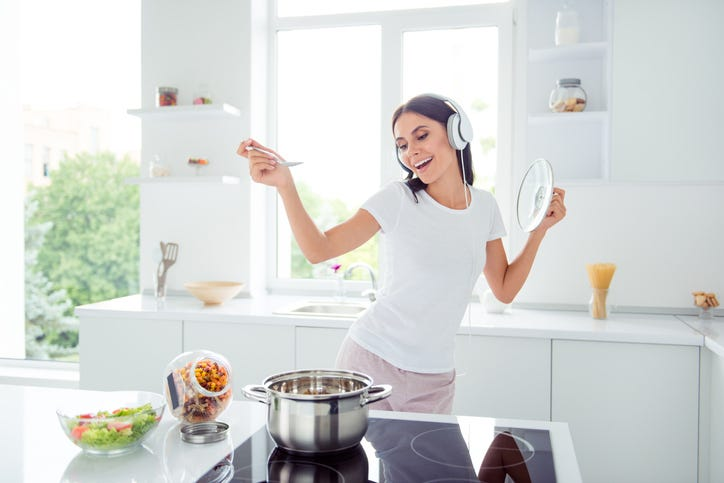 Woman cooking and listening to music