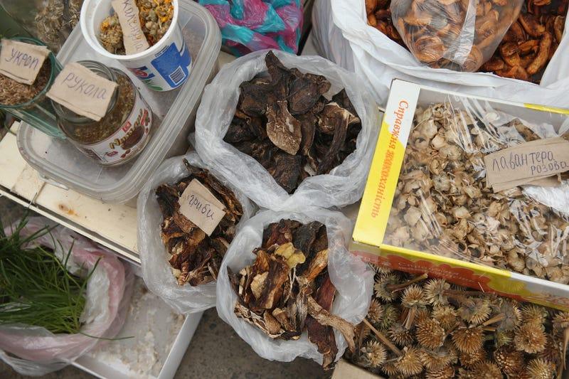 A vendor sells dried mushrooms
