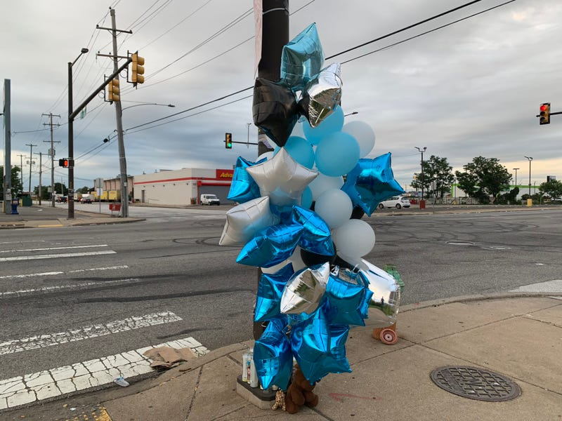 Balloons, candles and stuffed animals adorn a post at Butler Street and Aramingo Avenue in Port Richmond, where a 21-year-old man was shot and killed late Saturday night.