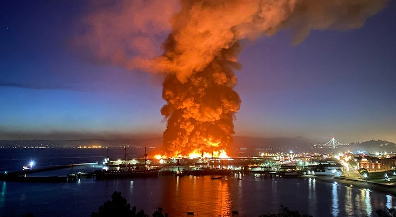 Roughly 100 firefighters are battling a four-alarm fire at a warehouse building at Fisherman's Wharf in San Francisco.