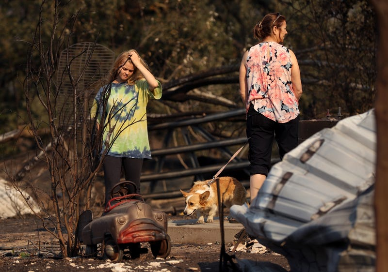 Ashley LaFranchi (L) and Stephanie LaFranchi (R) walk through a family home that was destroyed by the Kincade Fire on October 28, 2019 in Calistoga.