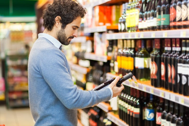 man checks price on wine bottle