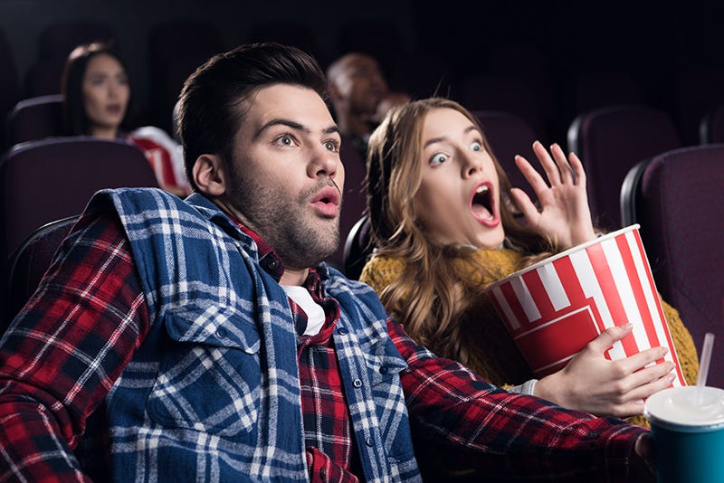 young shocked couple with popcorn watching movie in cinema