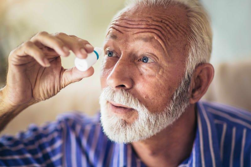 An old man uses eye drops
