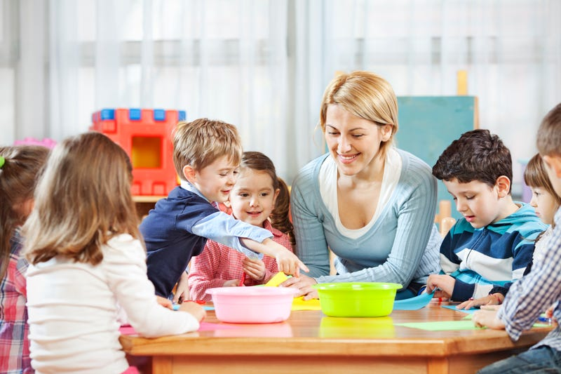 A baby sitter sits with several children around a table with paper and colored pencils