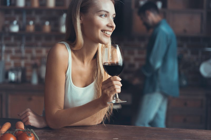 woman enjoying glass of wine at the bar