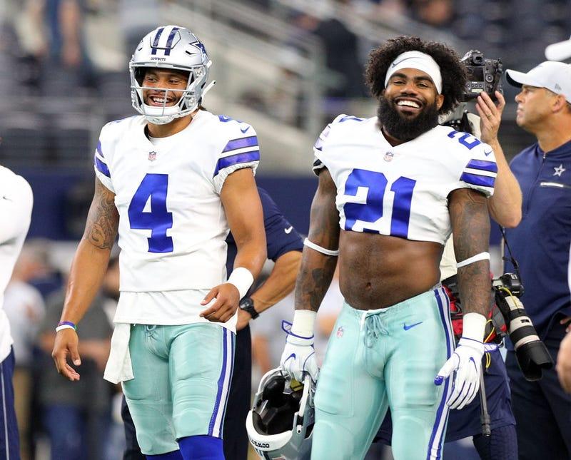Dak Prescott #4 of the Dallas Cowboys and Ezekiel Elliott #21 of the Dallas Cowboys smile during warm ups before the preseason game against the Arizona Cardinals at AT&T Stadium on August 26, 2018 in Arlington, Texas.