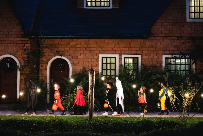 line of trick or treaters walking up to house