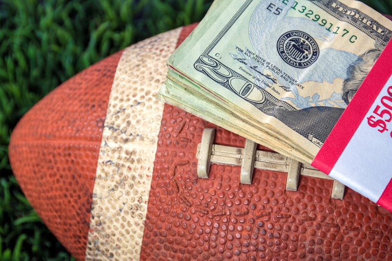 Football with a stack of cash on top.