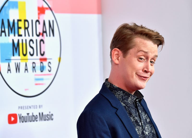 macaulay culkin with a cheeky smirk on the runway at the american music awards
