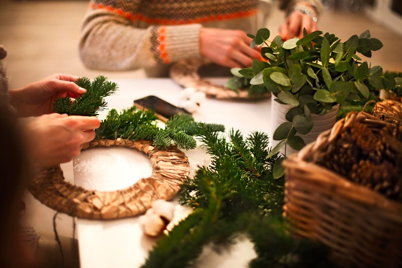 The hands of two unseen people arrange garlands on Christmas wreaths