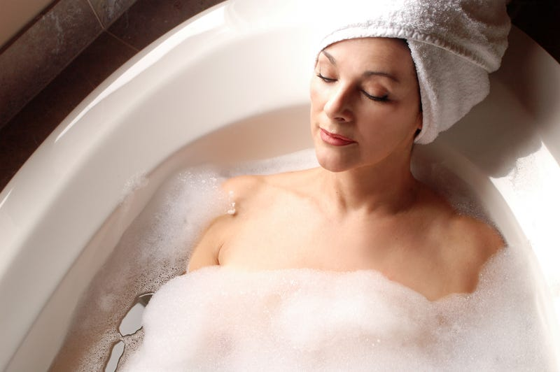A woman with a towel wrapped around her head lies in a sudsy bath