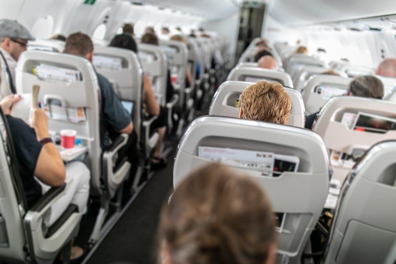Interior of commercial airplane with passengers in their seats during flight