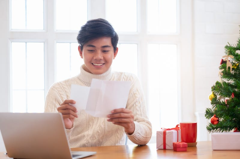 A man opens an envelope smiling at the card inside, with a Christmas tree and gifts nearby