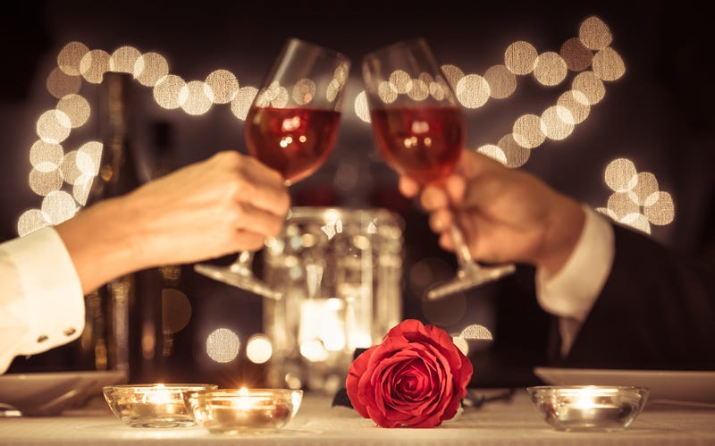 Two people toast with wine in the background of a table set with a rose and candles