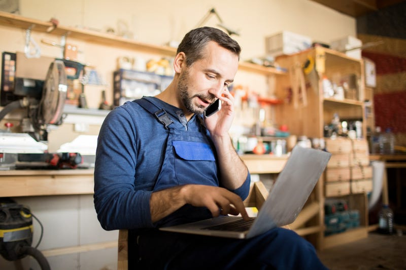 A man in a wood shop sits with a computer while talking on the phone