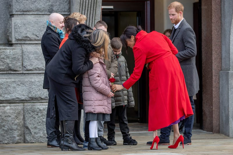 meghan markle and prince harry greet children outside as they visit a new statue to mark the 100th anniversary of the death of poet Wilfred Owen