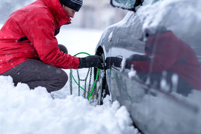 A man kneels down in the snow to apply snow chains to the tires of his car