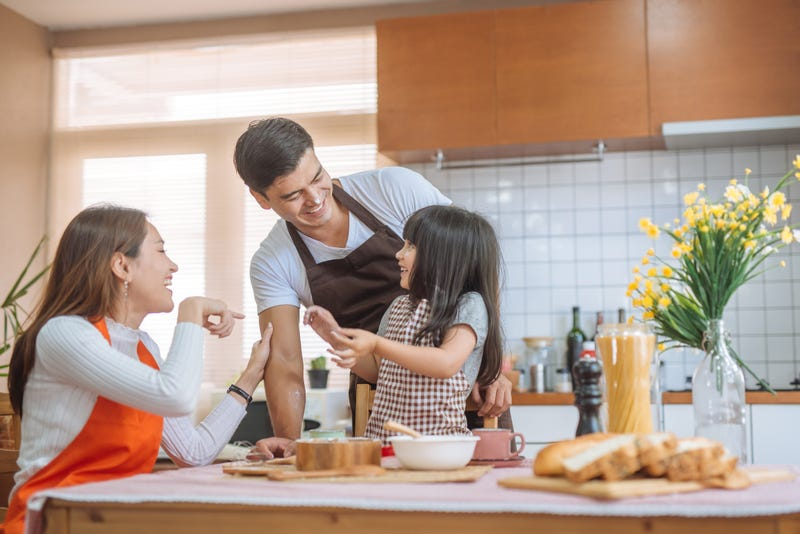 Parents and a young daughter fool around while cooking