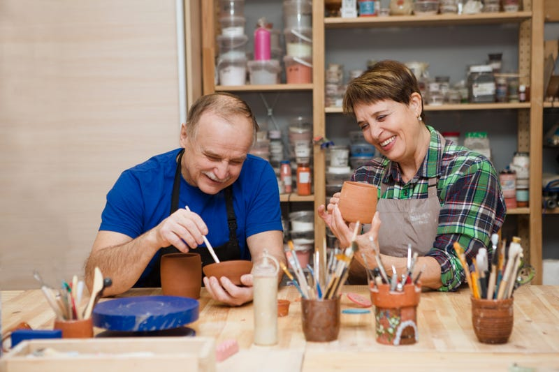 An older couple sit at a work bench painting pottery