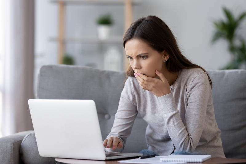 A woman looks at her computer in shock