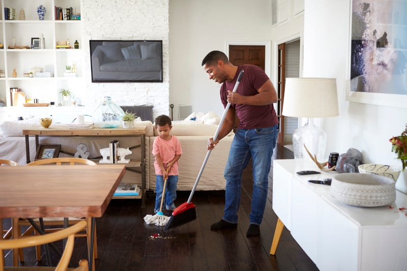A father/grandfather and little boy sweep a living room floor